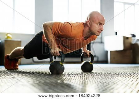 Intensive training in modern gym illuminated with bright sunlight: bald middle-aged sportsman standing in plank position with help of kettlebells, full-length portrait