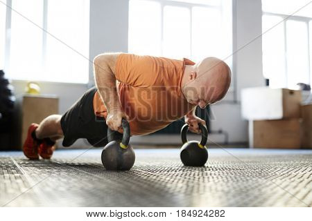 Bald bodybuilder looking down with concentration while doing plank exercise with kettlebells, full-length portrait