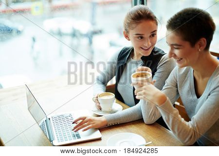 Attractive young women drinking delicious cappuccino and chatting animatedly while gathered together in coffeehouse, waist-up portrait