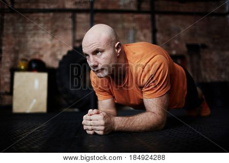 Bald middle-aged man doing plank exercise while having intensive workout in modern gym, full-length portrait