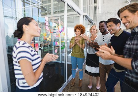 Happy business people applauding while standing against plan on glass wall in office