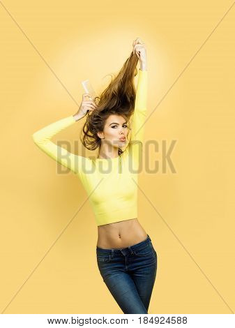 girl or pretty woman fashion model in stylish yellow top with sexy belly combing wavy blond long hair with comb on orange background. Hairdressing and beauty salon