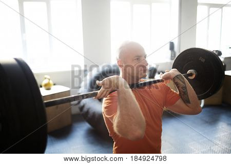 Concentrated bodybuilder doing shoulder press exercise with barbell in gym illuminated with bright sunlight