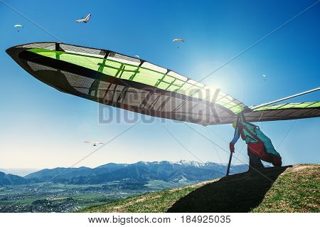 Hang-glider starting to fly from the mountain peak .