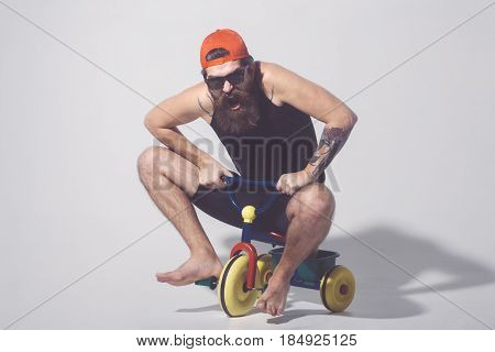 Bearded Shouting Man On Colorful Bicycle Toy In Sunglasses, Cap