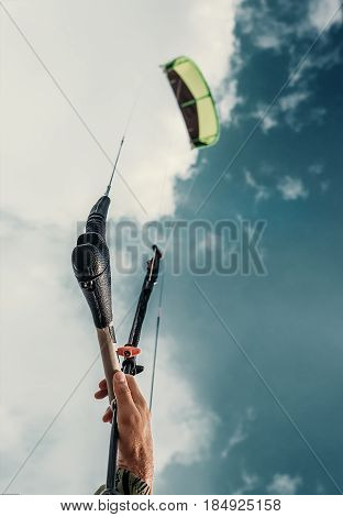 Close up image kitesurfer's hand with kite in blue sky