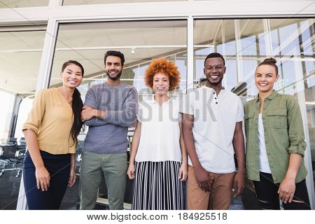 Portrait of smiling business colleagues standing side by side against glass wall in balcony