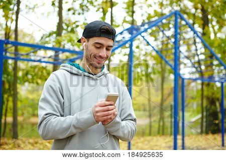 Waist-up portrait of joyful young sportsman listening to music on smartphone in order to psych himself up for effective workout
