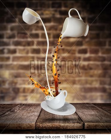 Splashing liquid of coffee and milk into white cup placed on wooden table. Coffee beans falling to hot drink