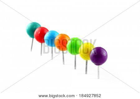Row of colorful thumb tacks