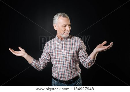 How to react. Positive elderly man turning his head looking sideways keeping arms bent in elbows