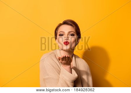 I Send A Kiss For You! Cute Young Girl With Nice Make Up Wearing Beige Cardigan Is Standing On The B