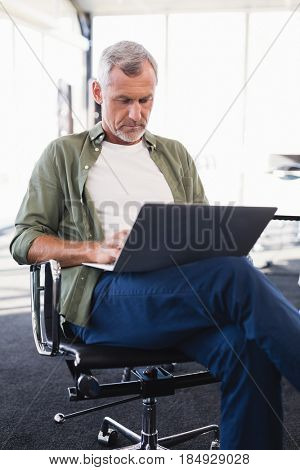 Businessman using laptop while sitting on chair in office