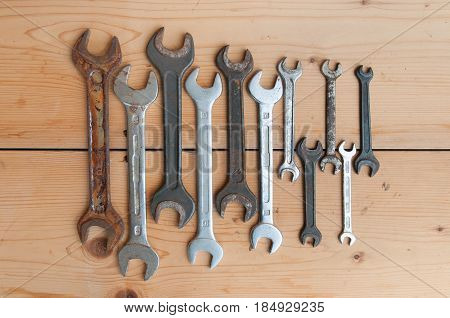 Old wrenches and pliers on wooden background. Set of tools. Top view