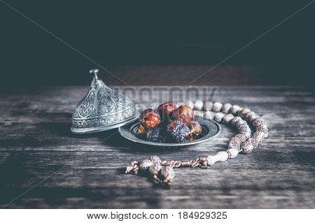 Date-palm is placed on silver. date palm fruits or kurma ramadan on a wooden black background.