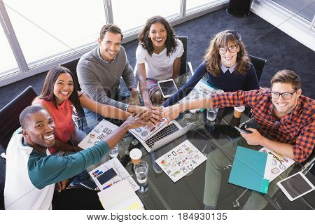 High angle portrait of happy business people stacking hands while sitting at desk in office