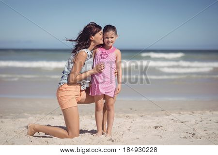 Happy mother kissing her daughter at beach during sunny day