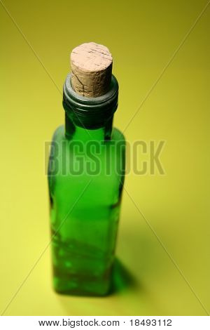 Green bottle with a cork attached. Focus is on the cork.