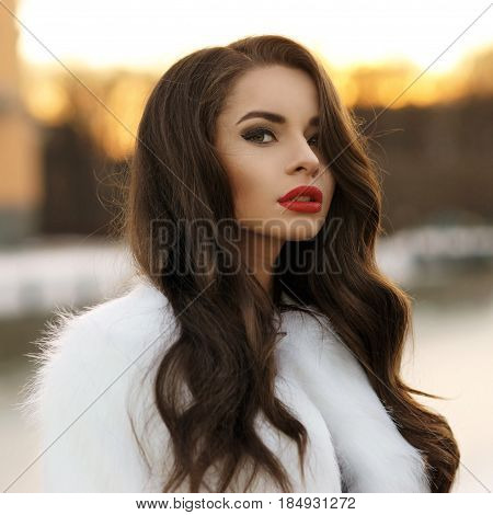 Breast portrait of young beautiful pretty woman with long curly hair and red lips posing outdoors at winter in white fur coat