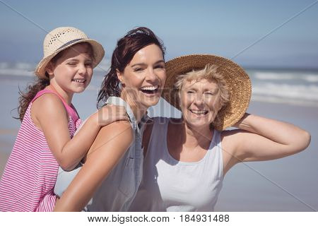 Portrait of cheerful multi-generation family at beach during sunny day
