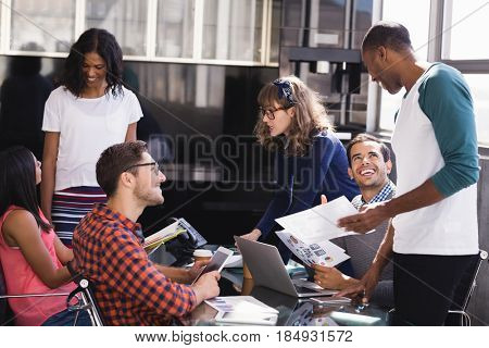 Colleagues discussing at desk during meeting in office