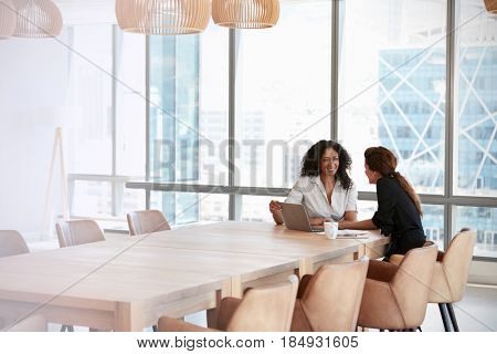 Two Businesswomen Using Laptop In Boardroom Meeting