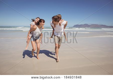 Happy parents piggybacking their children at beach against clear blue sky
