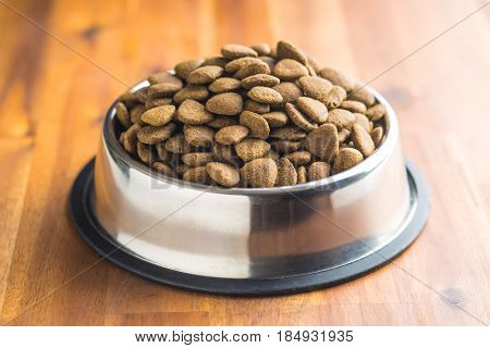 Dry kibble dog food in metal bowl on wooden table. poster