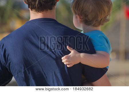 back view of father holding toddler son close together
