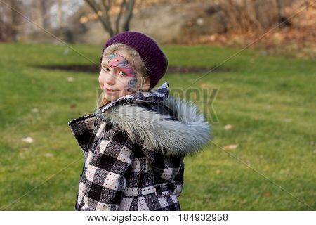 Adorable school age girl with facepaint walking outside in wintertime