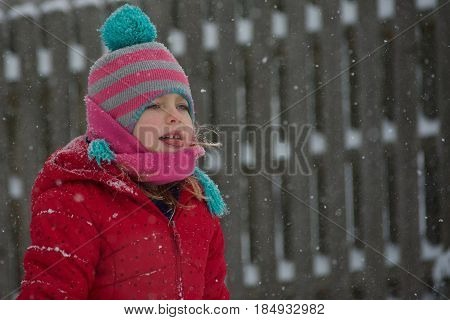 Adorable school age girl catching snowflakes on tongue outside in wintertime