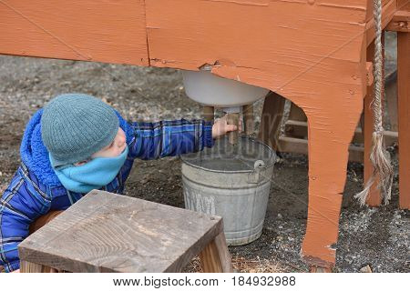 Adorable toddler boy practicing milking a pretend cow outside in wintertime