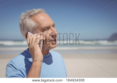 Senior man talking on mobile phone at beach during sunny day