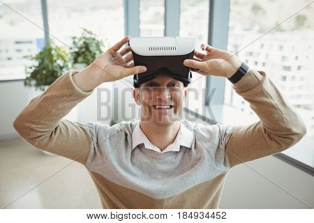 Portrait of happy executive using virtual reality headset in office