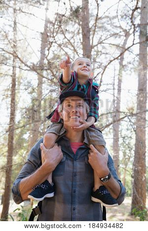 Low angle view of father carrying son on shoulders while pointing in forest
