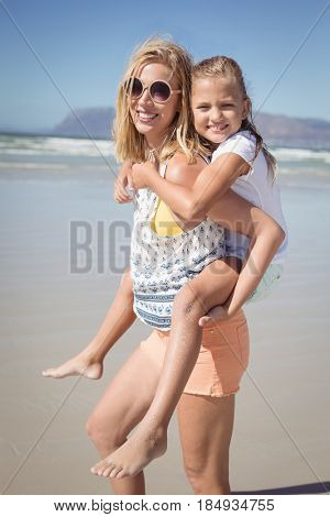 Portrait of happy mother piggybacking her daughter at beach during sunny day