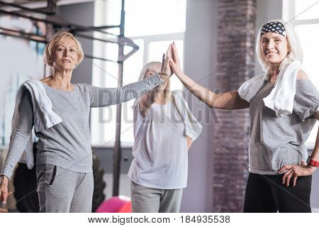 We are the best. Delighted sporty elderly women standing in a circle and giving each other a high five while resting after an intensive workout