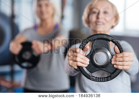 Physical activities. Selective focus of a weight disc being held by a nice active aged woman while doing physical activities