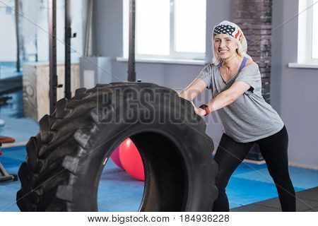 Physical strength. Happy well built active woman smiling and pushing a huge tire while exercising in the gym
