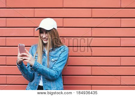 Portrait of positive girl in a cap hipster denim jacket and bright street background. She posts her friend and smiling
