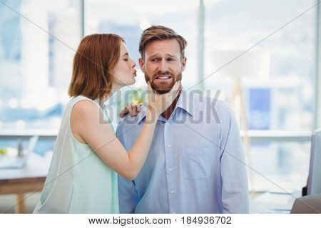 Affectionate woman kissing man in office