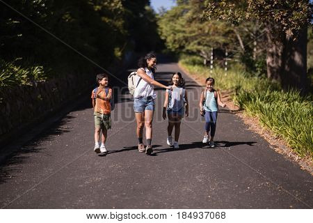 Happy kids and teacher walking on street during summer field trip