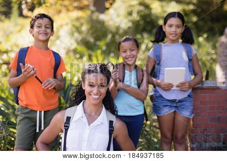 Portrait of happy teacher and students standing at nature reserve