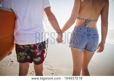 Mid section of couple holding hands at beach during sunny day