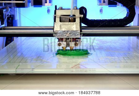 3D printer prints the form of molten plastic green close-up. Automatic three dimensional 3d printer performs plastic modeling in laboratory. Progressive modern additive technology