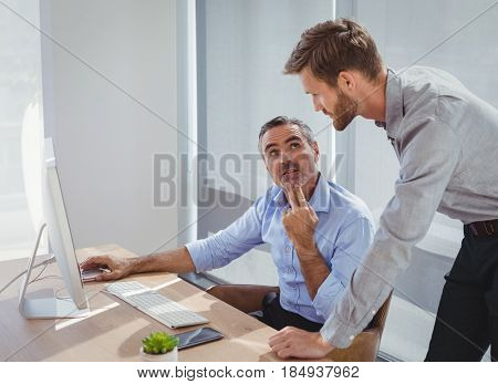 Executives interacting while working at desk in office