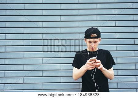 Student in cap and shirt listening to music on headphones typing on your phone. A young man talking on the Internet and listening to music on the background wall