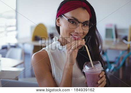 Portrait of smiling businesswoman holding drink in disposable glass at office