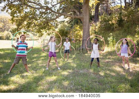 Group of cheerful friends playing with hula hoops on grassy field at campsite