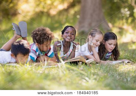 Friends reading book while lying on grassy field at campsite